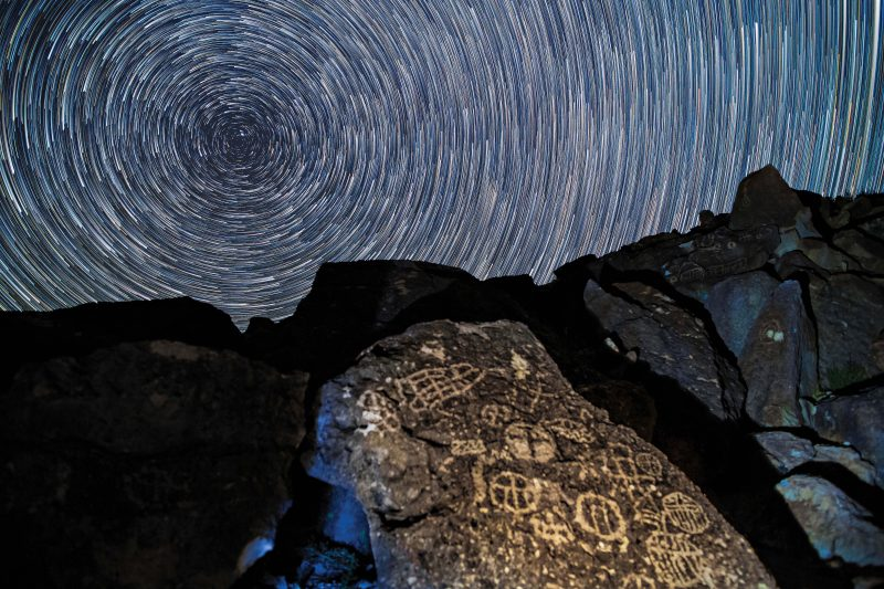 Concentric white circles filling the sky over large rock with symbols carved into it.
