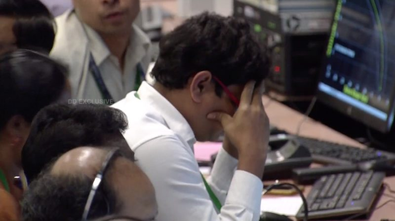 A dejected man at a computer terminal with his head in his hands.