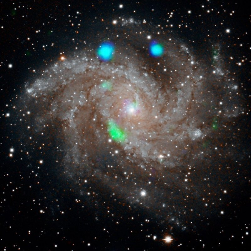 Spiral galaxy with oblong glowing green feature and two prominent blue spots.