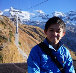 A young man wearing a blue jacket in a mountainous setting.