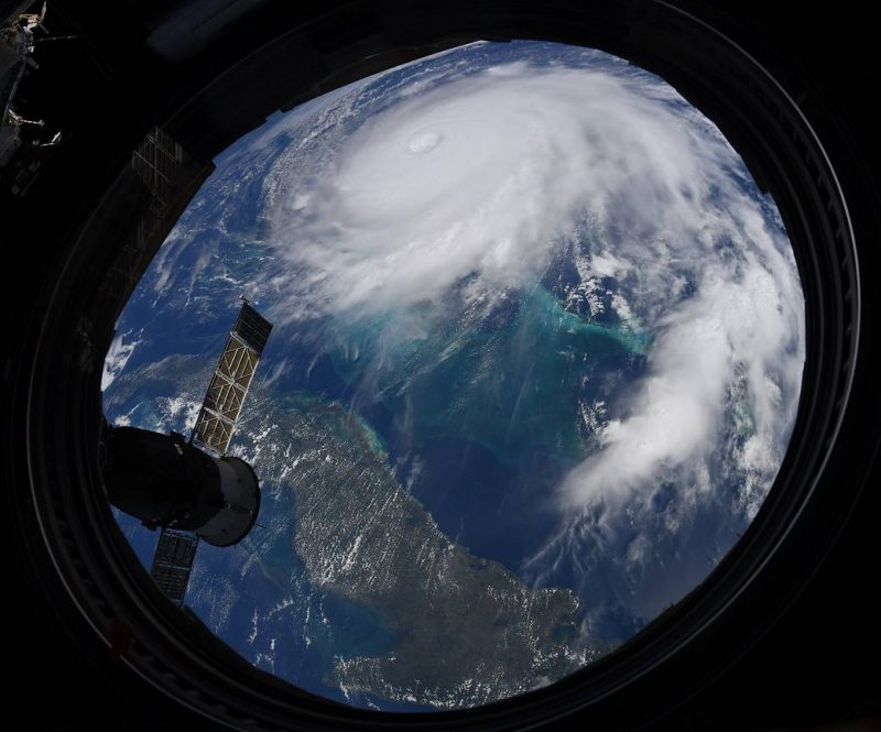 View from a round window aboard ISS of a powerful, swirling hurricane in the Atlantic.