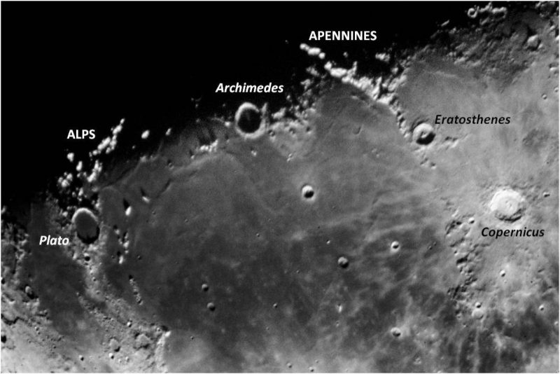 Labeled craters and mountain ranges at the edge between dark and light.