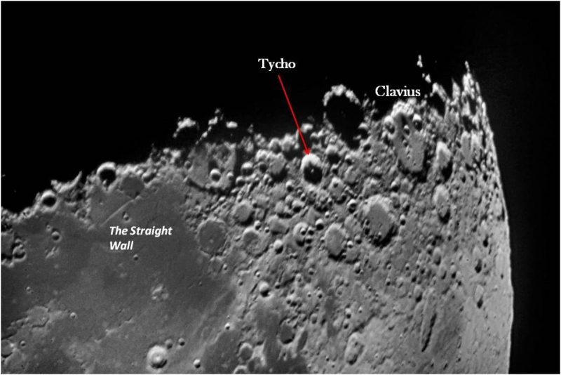 Craters and other features, including a short straight white line on a dark flat mare floor.