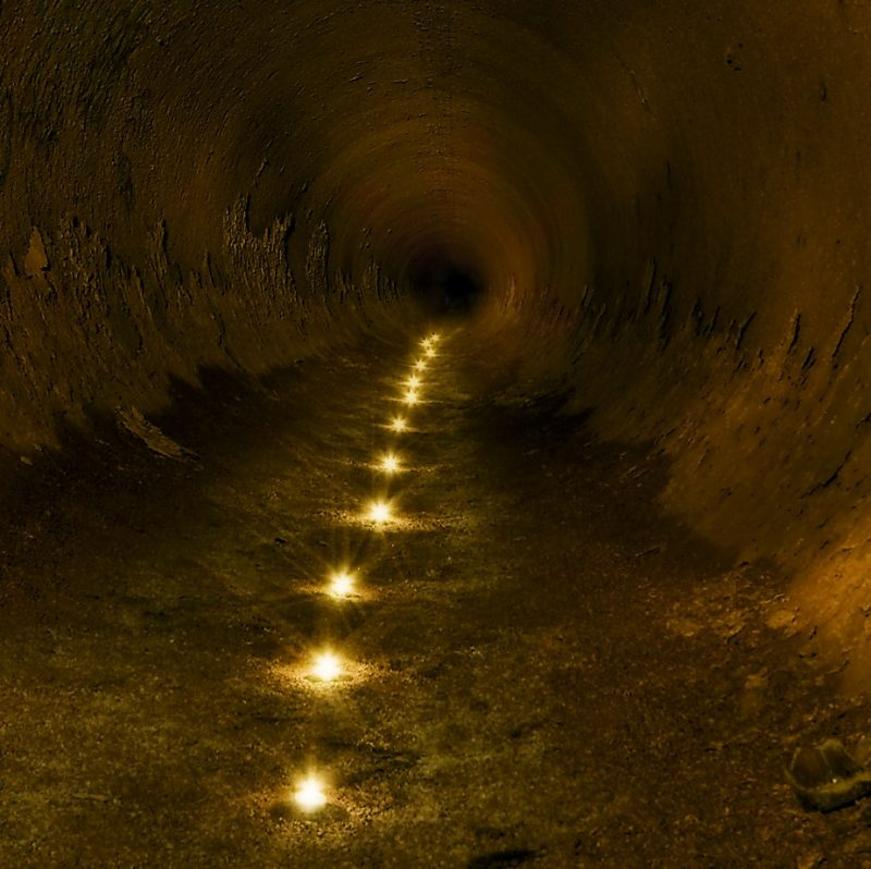 Illustration of lights in a tunnel, viewed from one end of the tunnel. The lights get fainter as they recede into the distance.