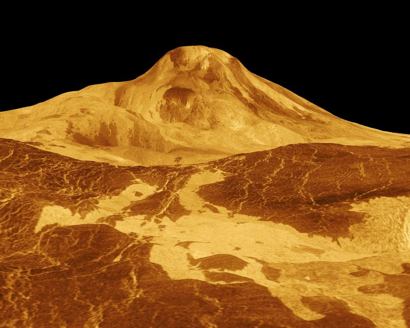 Orange image of a large shielded volcano with visible lava flows against a black sky.