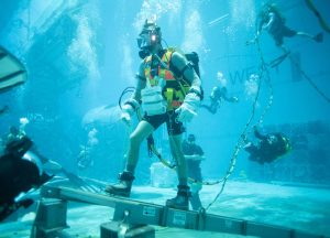 Person in gear in underwater tank, with other people floating around.