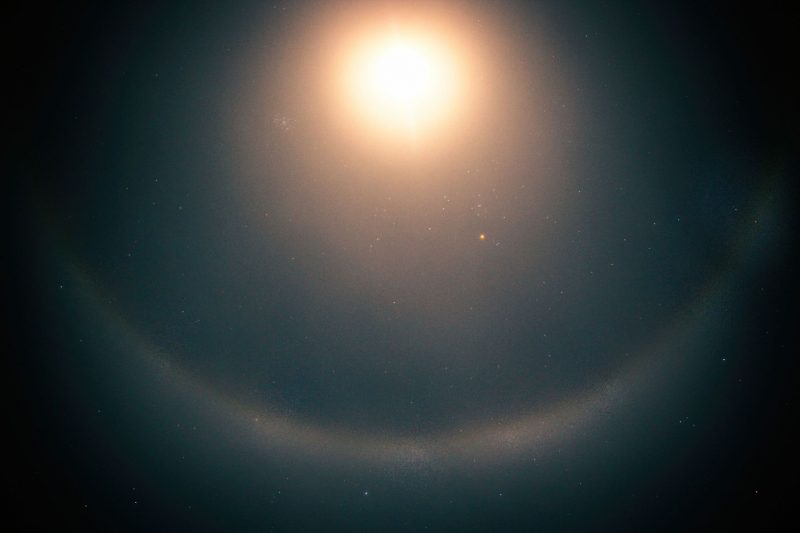 Bright moon, large lunar halo, bright red star and star cluster.