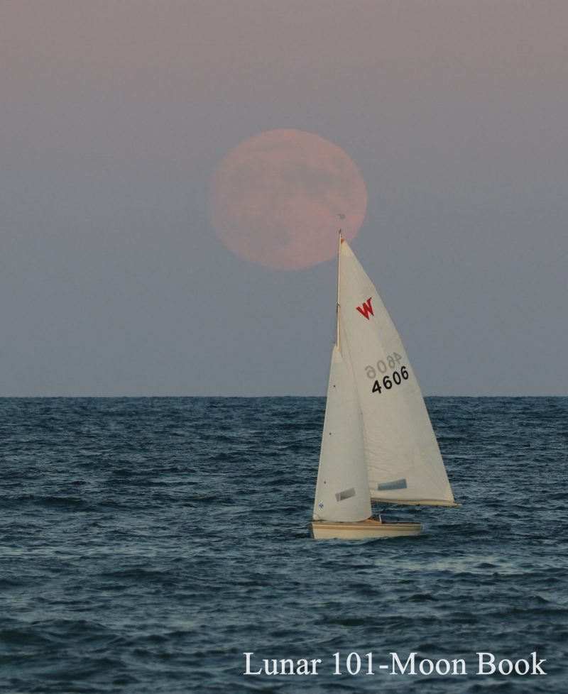 Sailboat on Lake Ontario with large pale pink Harvest Moon in lavender sky.