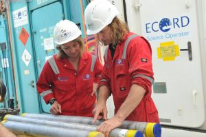 Two people in hard hats looking at core samples