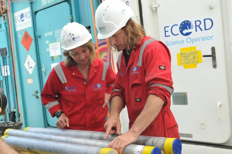 Two people in hard hats and red-orange jumpsuits looking at long gray cylinders lying on a table.