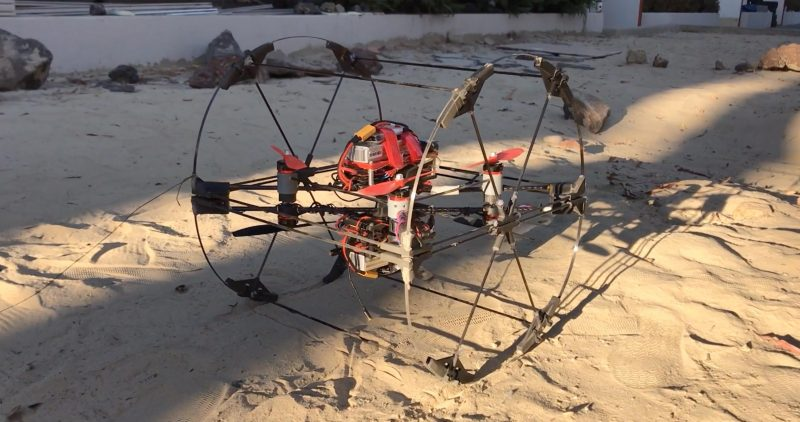 Small red machine with a large six-spoke wire wheel on each side rolling across sandy surface.