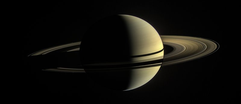 Saturn viewed via spacecraft, half illuminated with rings casting a shadow on the planet.