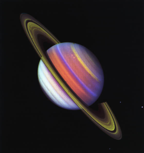 Saturn and its rings in false color with green rings and bands on planet in red, blue, and purple.