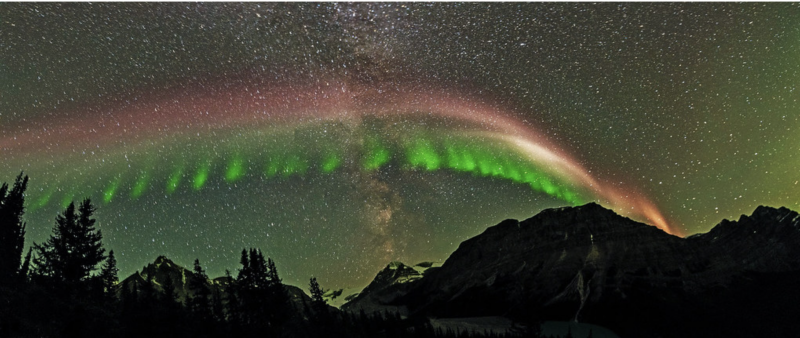 A vast, multicolored arc set against a background of green northern lights.