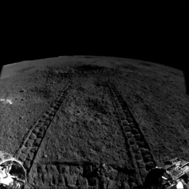 Rover tracks on rocky gray landscape with black sky.