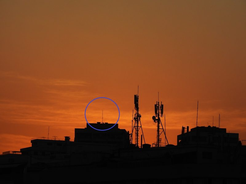 Orange twilight behind city roofline with blue circle around one distant radio tower.