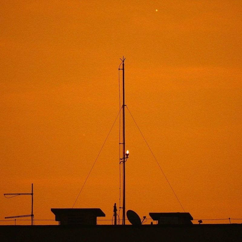 Brighter dot, fainter cot, in orange twilight above a roofline.