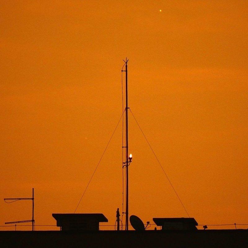 Brighter dot, fainter cot, in orange twilight above a roofline.