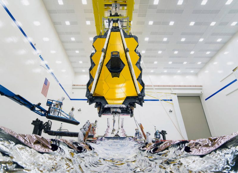 Array of large gold hexagons in clean room, above wide foil-covered other section of spacecraft.