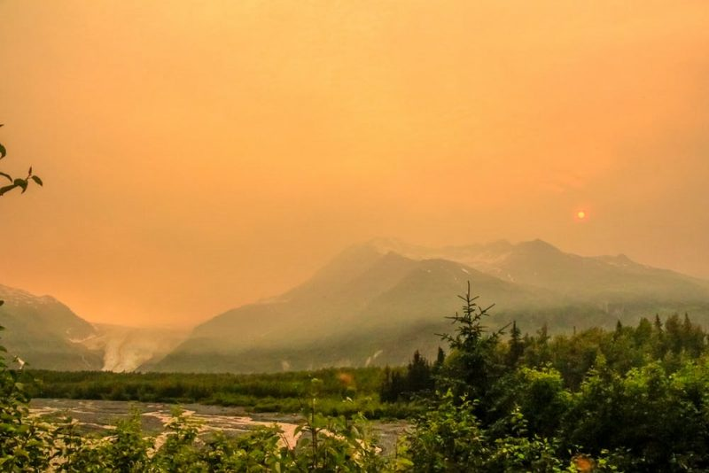 Glowing yellow-orange sky above mountainous landscapr with sun barely visible.