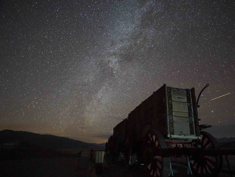 Star field with Milky Way and thin white streak on left of an old mining structure.