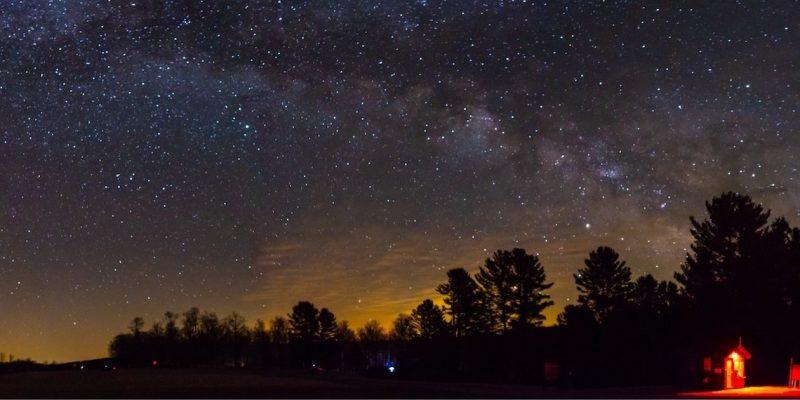Milky Way arcing across star field above dark woods.