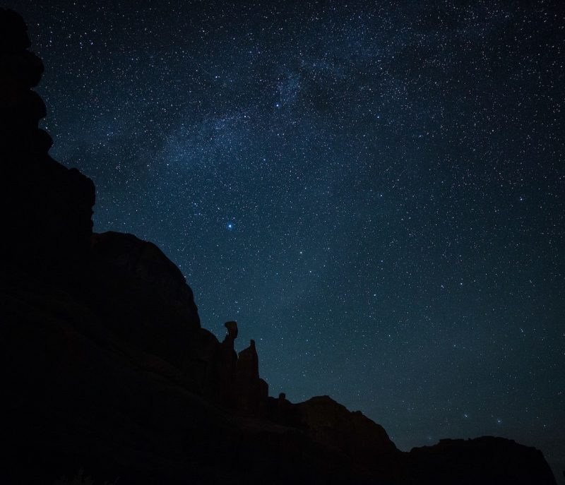 Star field with faint Milky Way above large sihouetted rock formations.
