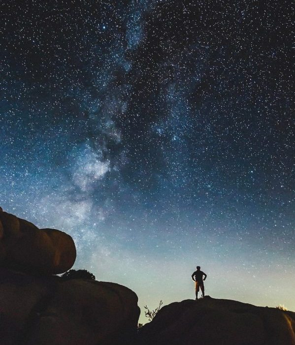 Silhouette of man standing on enormous rock with Milky Way rising in deep twilight.