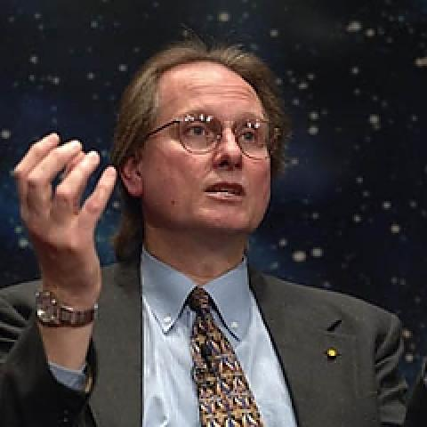 Man in suit gesturing with one hand against out-of-focus starry background.