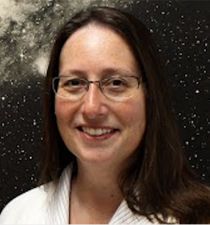 Smiling dark-haired young woman with glasses in front of astronomical mural.