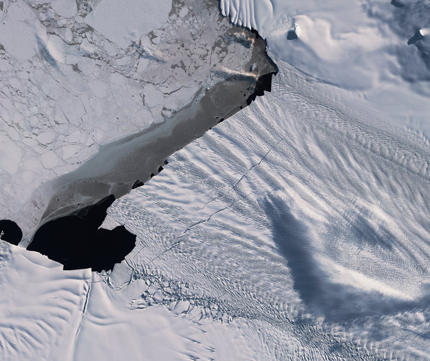 A long and wide crack in a glacier, showing dark sea water in the crack.
