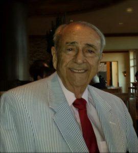 An older man in a seersucker suit and red tie.