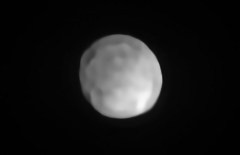 Roundish gray lumpy-surfaced asteroid with black space in background.