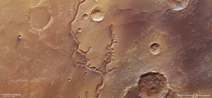 Natural color satellite view of tan landscape with craters and winding, darker river.