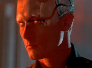 Head shot of a sinister robotic-looking man in red light.