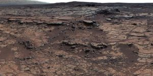 Rocky plain with hills in background on Mars.