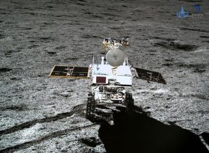 Rover on grey regolith with tire tracks.