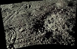 Edge of small crater in grey regolith with tire tracks.