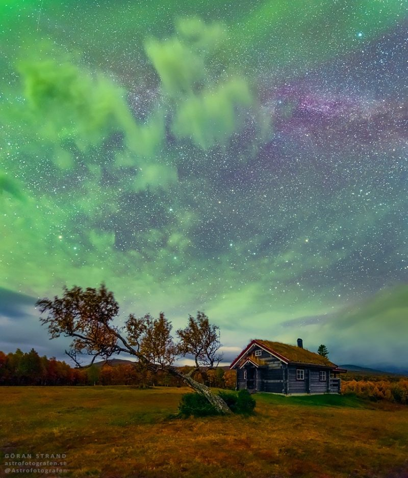 Landscape with green clouds, starry sky, and a small cabin.