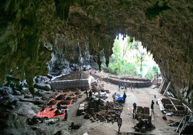 Equipment and people around holes dug inside cave mouth with lots of stalactites.