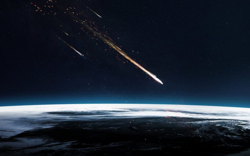 Flaming streak of light in a dark sky heading downward toward Earth viewed from orbit.