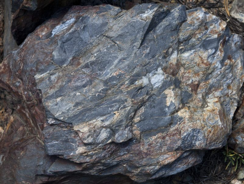 Rough, irregular gray rock with reddish-brown spots and streaks.