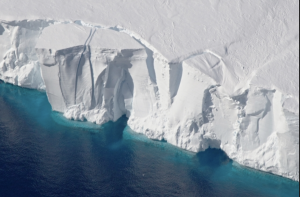A tall ice cliff, with cracks indicating a calfing of the ice into the sea soon.