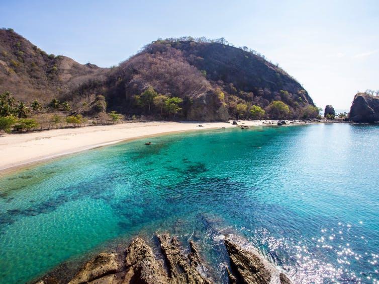 White sand beach, blue water, very steep hilly coastline.