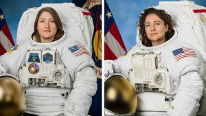 Two female astronauts in spacesuits with no helmets.