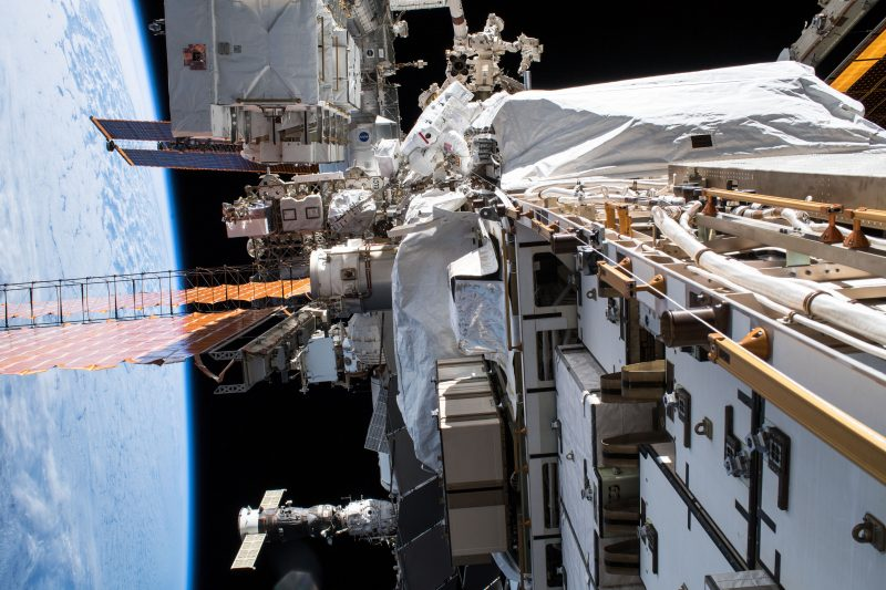 External view of one side of the International Space Station showing solar panels and complicated machinery.
