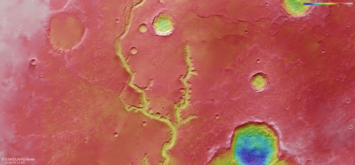 A wide valley on Mars. A river bed runs through it.