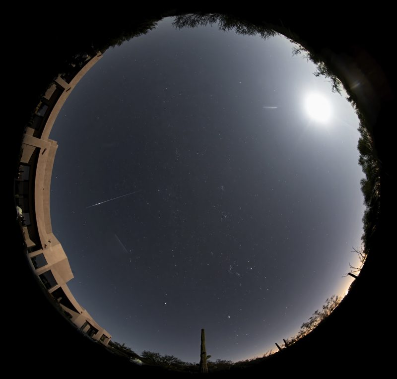 Round panorama of entire sky with nearly full moon and a short, thin bright streak.