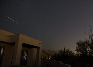 Bright, colorful fireball (shooting star) streaking above a house.