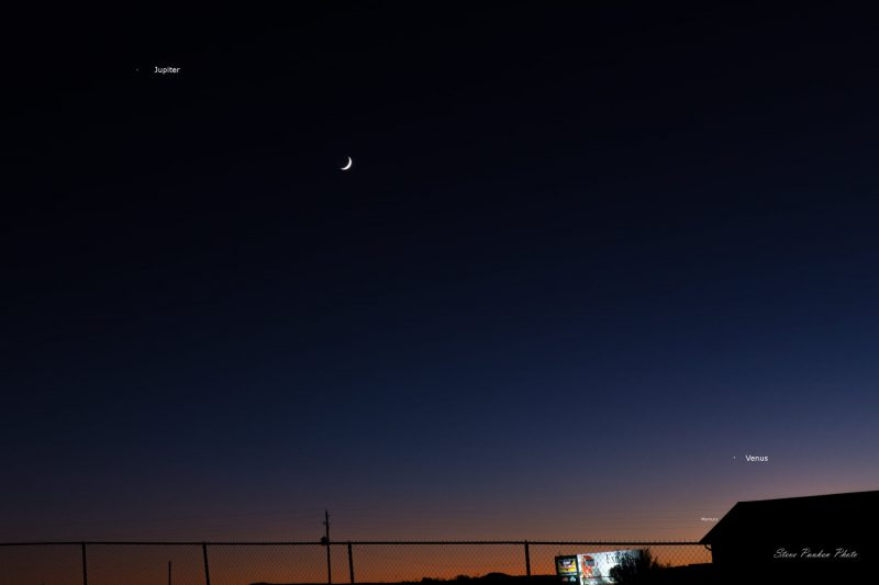 Thin crescent young moon between Venus and Jupiter at dusk.